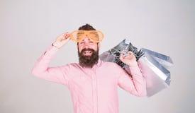 Reparto provechoso C?mo conseguir listo para sus vacaciones pr?ximas Inconformista barbudo del hombre con los bolsos de compras d foto de archivo