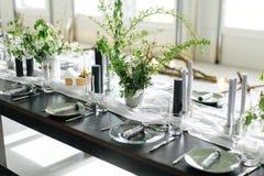 Repas élégants et une longue table, grenier Table noire, chaises, plats, bougies Banques avec des verts, fleurs Bougies noires Image stock