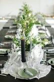Repas élégants et une longue table, grenier Table noire, chaises, plats, bougies Banques avec des verts, fleurs Bougies noires Photos libres de droits