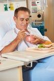Repas appréciant patient mâle dans le bâti d'hôpital image stock
