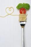 Repas de pâtes de nouilles de spaghetti avec l'espace de coeur et de copie sur une fourchette Photographie stock libre de droits