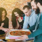 Repas de pizza de pause de midi de millennials d'?quipe d'affaires image libre de droits