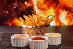 Repas de pommes frites avec des diverses sauces - devant la cheminée image libre de droits