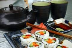 Repas de sushi avec la théière et la cuvette photographie stock libre de droits