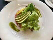 Repas gastronomique - tartre de thon et tranches d'avocat avec de la sauce asiatique verte Photos stock