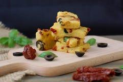 Repas gratuit de gluten de farine de maïs rôtie, de tomate sèche, d'olives noires et de basilic sur le bois sur le tissu de jute  photos stock