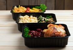 Repas pr?ts ? manger, conteneurs avec des ailes et des l?gumes crus de poulet frit sur le fond rustique, tomate-cerise et greenss images stock