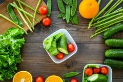 Repas sain dans des récipients Salade avec la tomate, concombre, orange dans des récipients sur la vue supérieure de fond en bois Images libres de droits