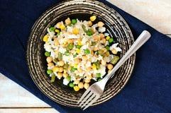 Repas sain de vegan avec du riz, les pois chiches, le maïs, les pois, les haricots verts et le riz du plat foncé sur le tissu de  Images stock