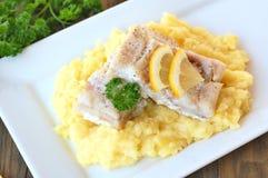Repas sain des poissons et de la purée de pommes de terre avec le citron et le persil du plat blanc sur le fond en bois de brun f Image stock