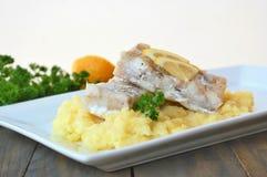 Repas sain des poissons et de la purée de pommes de terre avec le citron et le persil du plat blanc sur le fond en bois de brun f Photographie stock libre de droits