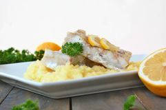 Repas sain des poissons et de la purée de pommes de terre avec le citron et le persil du plat blanc sur le fond en bois de brun f Photo libre de droits
