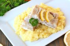 Repas sain des poissons et de la purée de pommes de terre avec le citron et le persil du plat blanc sur le fond en bois de brun f Photos stock