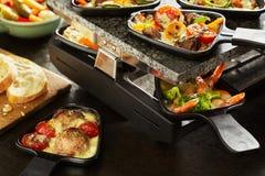 Repas savoureux de raclette avec les ingrédients assortis photographie stock