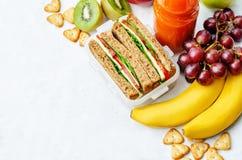 Repas scolaire avec un sandwich, des fruits frais, des biscuits et le jus photographie stock