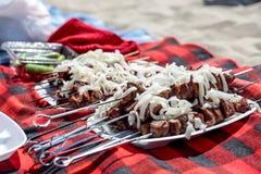 Repas sur une plage : le shashlyk prêt de chiches-kebabs de boeuf a complété à l'oignon blanc image libre de droits