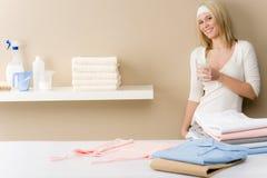 Repasser de blanchisserie - rupture de femme avec la boisson images stock