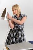 Repasser enthousiaste de femme au foyer Photographie stock libre de droits