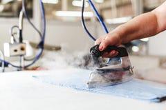 Repasser professionnel dans le détail de nettoyeur à sec du fer et des mains Photos libres de droits
