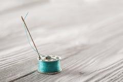 Repassez la bobine avec le fil bleu sur un fond en bois blanc Image stock