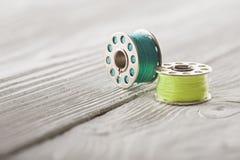 Repassez la bobine avec le fil de bleu et de jaune sur le fond en bois Image libre de droits