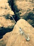 Repassez la corde tordue étirée entre les roches dans la correction de grimpeurs par l'intermédiaire du ferrata Corde fixe dans l Images libres de droits