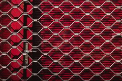 Repassez la texture d'un gril en acier sur les volets rouges sur la porte Fond rouge images libres de droits