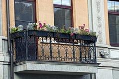 Repassez le balcon et les pots de fleurs avec les fleurs rouges avec une fenêtre sur un mur brun Image stock