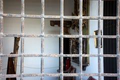 Repassez le grillView de fenêtre de la rue dans la salle par un vieux gril rouillé en métal Photos stock
