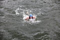 Repassez le nageur d'homme dans le chapeau et le wetsuit respirant en exécutant la course de papillon Photographie stock libre de droits