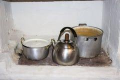 Repassez les pots, bouilloire pour faire cuire sur le fourneau du feu dans la cuisine Photos stock