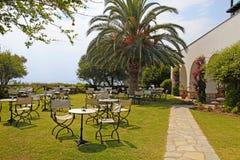 Repassez les tables et les chaises dans le jardin, Grèce Photographie stock