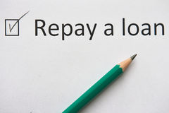 Repay a loan CREDIT. To fulfill set goal. phrase `Repay  loan` is written on white paper in pencil, marked with tick. Repay a loan CREDIT. To fulfill set goal Stock Images
