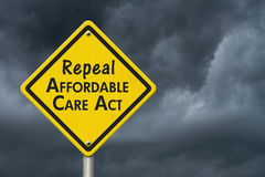 Repealing and replacing the Affordable Care Act healthcare insurance. Yellow warning highway road sign with words repeal Affordable Care Act with stormy sky stock image