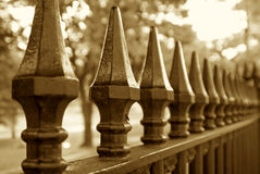 Repeating points. Sepia toned image of wrought iron fence trailing off into the distance Stock Image
