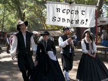 Repent Sinners!. A group of four carrying a banner to convince Sinners to Repent. All dressed up in costumes from the Renaissance epoch. At the Renaissance fair Stock Photos