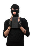 Repentant robber with the Bible Royalty Free Stock Image