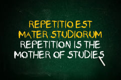 Repetition. Is the mother of studies. Latin quote handwritten with chalk on a green school board royalty free stock photography