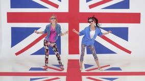 Repetition av två nätta roliga flickor som dansar i studio med tapeter av UK-flaggan arkivfilmer