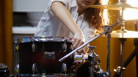 Repetition. Ginger girl plays drums raid. The girl fixing snare. Studio stock images