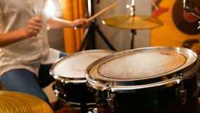 Repetition. Ginger girl plays on drums in the studio. Focus on drums. Mid shot royalty free stock photography