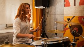 Repetition. Ginger girl plays on drums in the studio. Focus on girl. Mid shot royalty free stock images