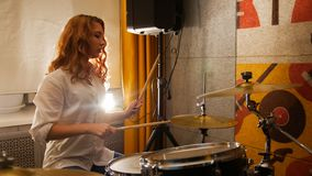 Repetition. Ginger girl plays on drums in the studio. Mid shot royalty free stock images
