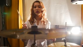 Repetition. Ginger girl plays on drums in the studio. Portrait. Repetition. Ginger girl plays on drums in the studio.Portrait. Mid shot stock photography