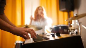 Repetition. Girl drummer and a guy on keyboards. Focus from hands to drums. Backlight. Studio royalty free stock photography