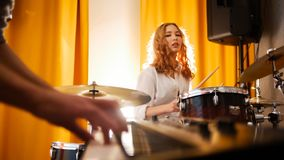 Repetition. Girl drummer and a guy on keyboards. Focus from hands to drums. Studio stock images