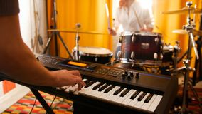 Repetition. Girl drummer and a guy on keyboards. Focus on keyboard. Studio stock photography