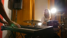 Repetition. Girl drummer and a guy on keyboards. Hands in focus. Studio royalty free stock photo