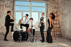 Free Repetition Of Multi Ethnic Jazz Band In Loft. Bass Guitar Player, Electric Guitar Player, Saxophonist And Drummer At Royalty Free Stock Photography - 183342177