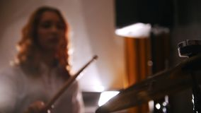 Repetition. Redhead girl plays on drums. makes and stops vibration of drum plate Slow motion. Focus on drums